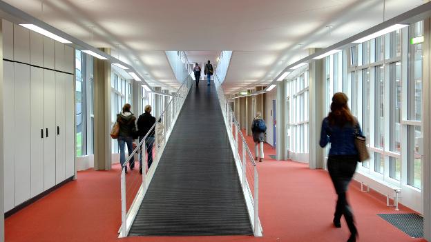 Studierende auf dem Gang einer Hochschule.